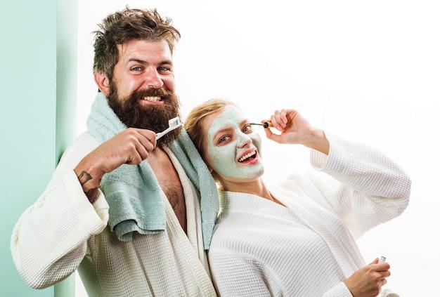 아침 치료. 커플 욕실에서. 남편과 아내. 칫솔을 든 남편, 화장품 페이셜 마스크를 쓴 아내.