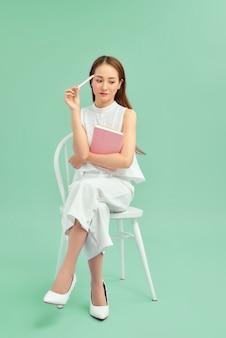 朝の雰囲気。青い壁の上の椅子に座って、本を読んでいる女の子