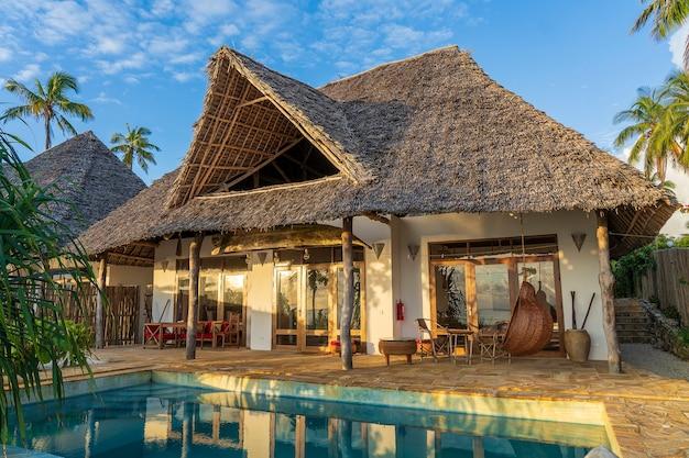 Утренний вид на роскошную виллу на тропическом пляже у моря на острове занзибар, танзания, восточная африка
