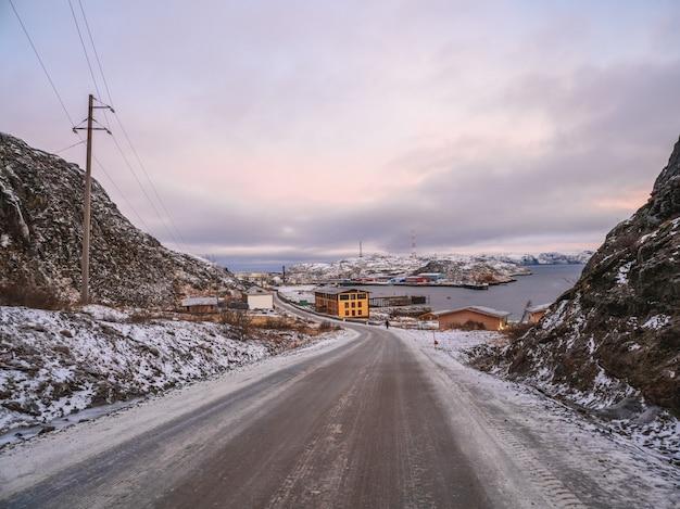 Утренний вид на прибрежный рыбацкий городок териберка, на севере кольского полуострова. шоссе среди арктических холмов. россия.