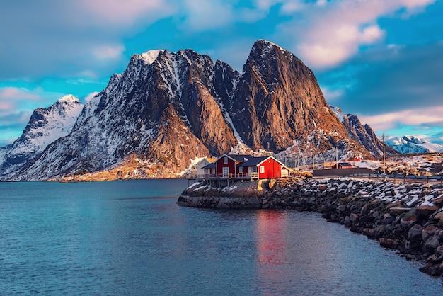 Утренний вид на знаменитую туристическую достопримечательность рыбацкой деревни хамной на лофотенских островах, норвегия, с красным домом рорбу зимой