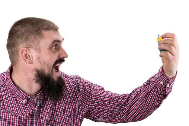 朝の目覚めの概念。猛烈な顔をした男は目覚まし時計を持っています。白い背景で隔離。