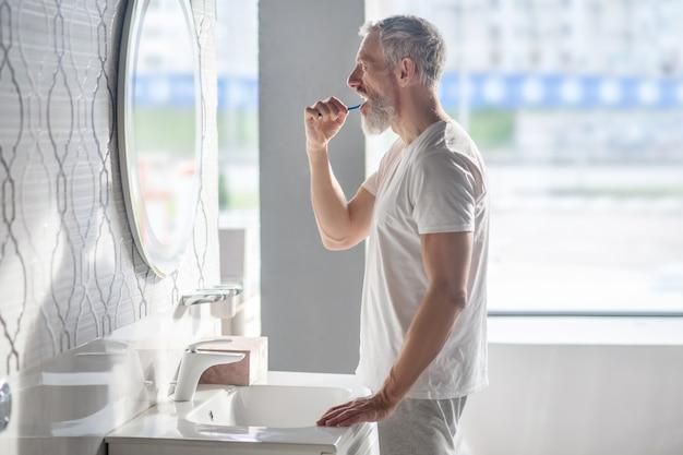 Утро, умывание. седовласый бородатый мужчина в белой футболке чистит зубы перед зеркалом в хорошем настроении
