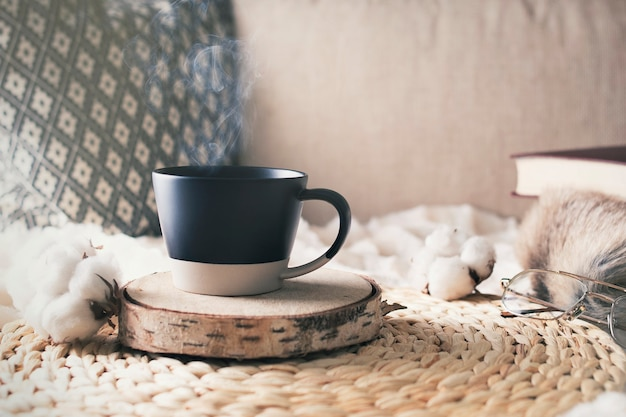 Morning of weekend with cup of coffee and book on bed