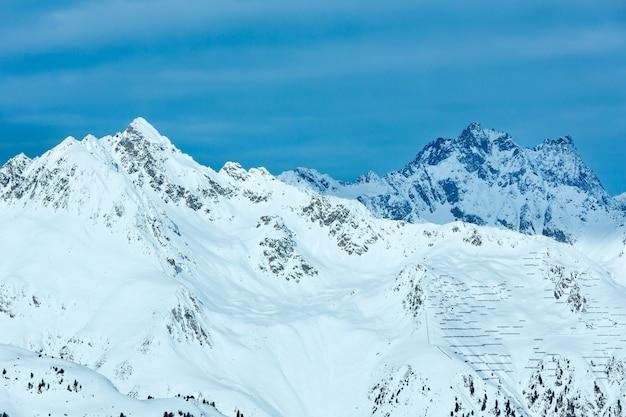 Утренний зимний пейзаж сильвретта альпы с барьерами для удержания снега на склоне (тироль, австрия).