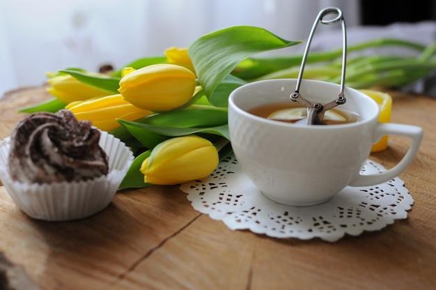 나무 테이블에 마시멜로와 노란 튤립을 넣은 녹차 한 잔과 함께 아침. 침대에서 아침 식사