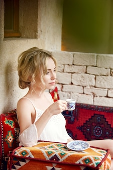 Morning woman drinking coffee resting sitting on a turkish sofa. woman dreaming, beautiful blonde hairstyle, hot tea in a cup in her hands