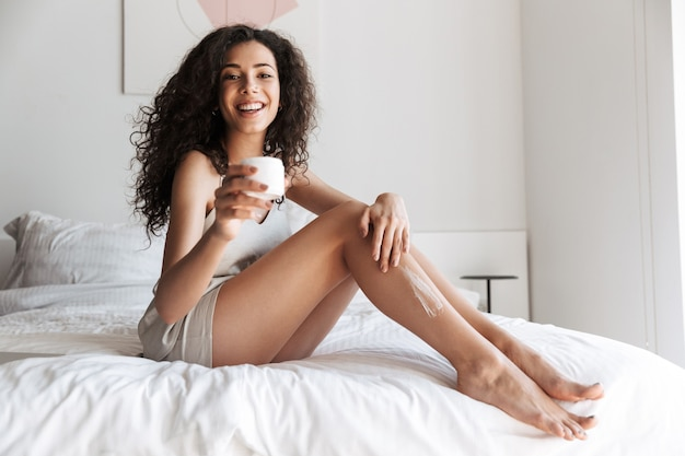 Morning woman with long curly hair sitting on bed with white clean linen at bedroom, and applying body cream on her legs
