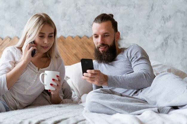 Планирование утреннего рабочего дня. молодой мужчина и женщина в постели звонят и проверяют смартфон.