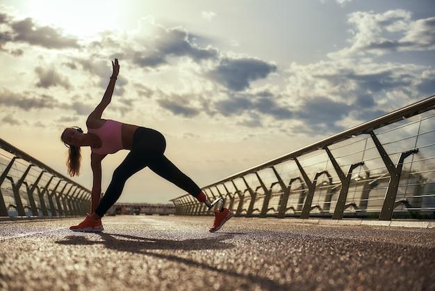 Утренняя тренировка на всю длину молодой женщины-инвалида с протезом ноги в спортивной одежде, занимающейся йогой