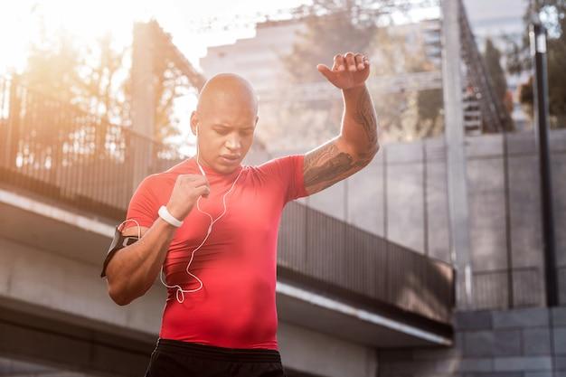 朝のトレーニング。屋外で一人でトレーニングしながらヘッドフォンで音楽を聴くハンサムな若いスポーツマン