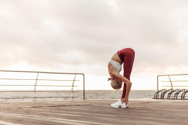 Утренняя тренировка концепция здорового образа жизни молодая привлекательная женщина в спортивной одежде разогревается перед тренировкой