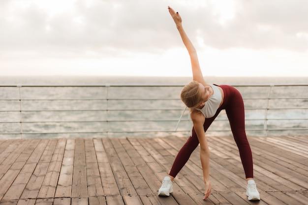 Утренняя тренировка концепция здорового образа жизни молодая привлекательная женщина в спортивной одежде действительно разогревается