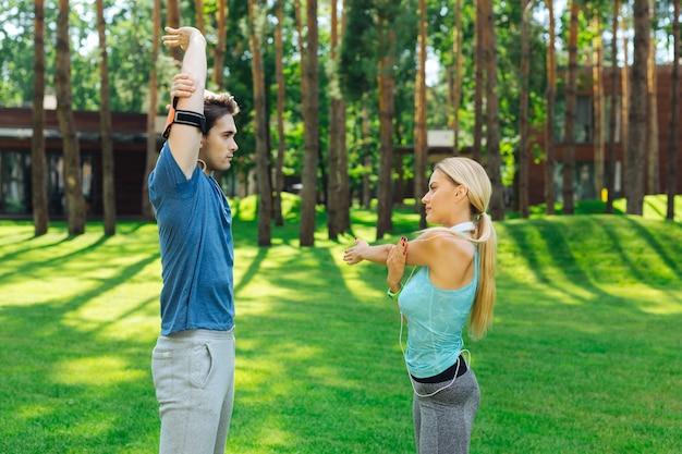 Утренняя тренировка. хорошие позитивные люди стоят друг напротив друга во время утренней тренировки