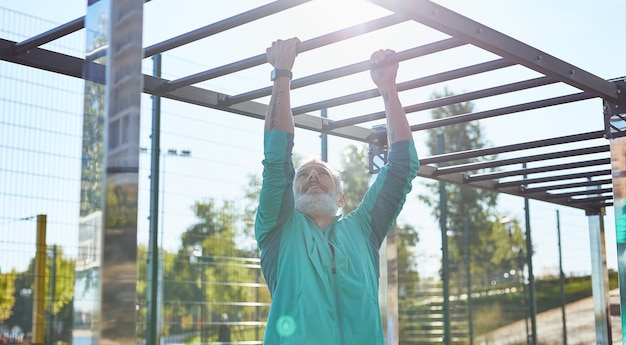 Утренняя тренировка сильный и здоровый бородатый пожилой мужчина в спортивной одежде делает подтягивания на турнике