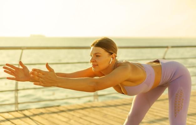 아침 운동. 훈련 전 워밍업. 일출에 해변에서 스트레칭을 하는 운동복을 입은 젊은 여성