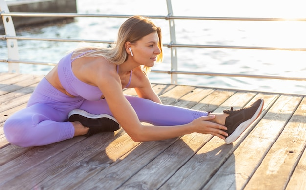 Morning workout. warming up before training. young fit woman in sportswear doing leg stretching while sitting on the beach pier at sunrise