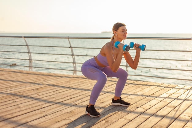 Morning workout. young slim woman in sportswear practicing squats with dumbbells in hands on the beach at sunrise