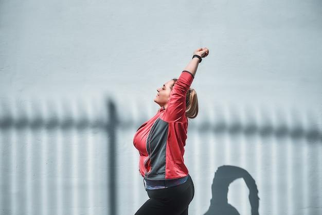 朝のヨガ。屋外でウォーミングアップしながらストレッチスポーツ服を着た若いプラスサイズの女性の側面図。減量。スポーツコンセプト