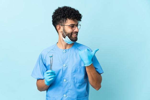 製品を提示する側を指している青い背景に分離されたツールを保持しているモロッコの歯科医の男