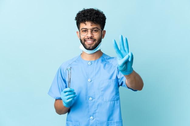 青い幸せに分離されたツールを保持し、指で3を数えるモロッコの歯科医の男