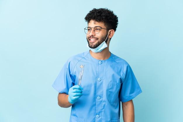 Марокканский дантист мужчина держит инструменты, изолированные на синей стороне
