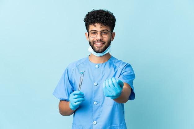 모로코 치과 의사 남자 손으로와 서 초대 파란색 벽에 고립 된 도구를 들고. 와줘서 행복해