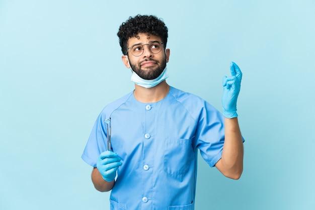 Марокканский дантист держит инструменты, изолированные на синей стене, скрещивая пальцы и желая всего наилучшего