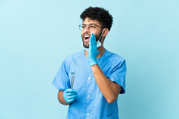 Мужчина-стоматолог из марокко, держащий инструменты на синем, кричит с широко открытым ртом в сторону