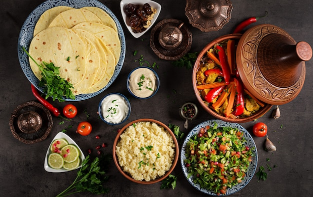 Moroccan food. traditional tajine dishes, couscous  and fresh salad  on rustic wooden table. tagine chicken meat and vegetables. arabian cuisine. top view. flat lay