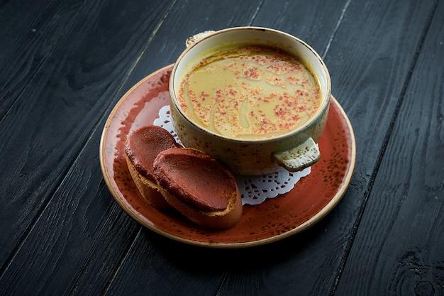 モロッコのハリラ、黒い木の背景に赤いプレートにコリアンダーとレンズ豆のスープ。