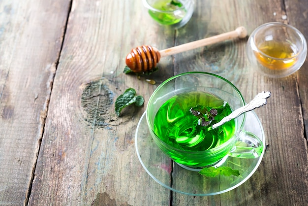 Moroccan mint tea with fresh mint leaves and honey on old wooden background