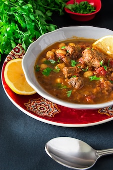 Moroccan soup harira with meat, chickpeas, lentil, tomato and spices. hearty, fragrant. preparing for iftar in the holy month of ramadan