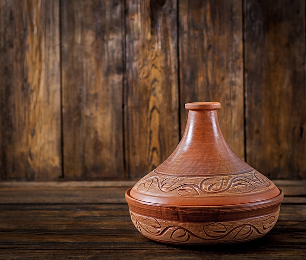 Moroccan tagine (cooking vessel) on a wooden table. copy space