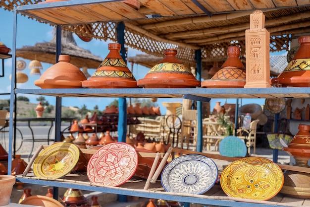 モロッコのエッサウィラにあるショップで販売されるモロッコのタジン陶器とセラミックプレート。