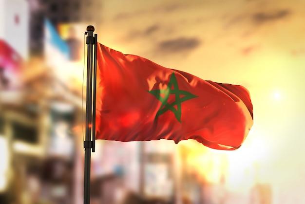 Марокко флаг против города размытым фоном на восход солнца подсветка