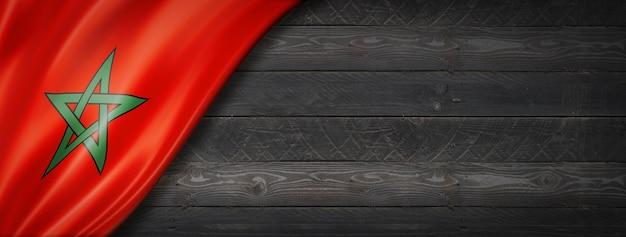 Morocco flag on black wood wall. horizontal panoramic banner.