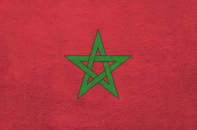 Morocco flag depicted in bright paint colors on old relief plastering wall.