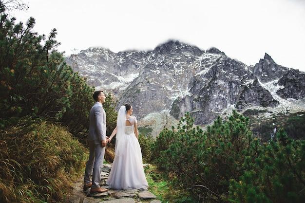 結婚式のカップルは、ポーランドのタトラ山脈の湖の近くを歩くmorskie oko