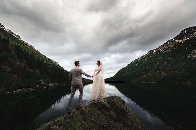 若い結婚式のカップルは湖morskie okoの岸にマウンテンビューを楽しんでいます