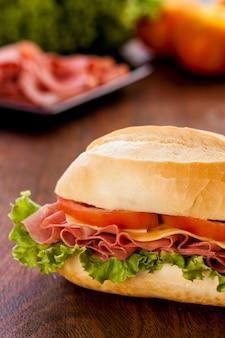 Бутерброд mortadela на деревянном столе.