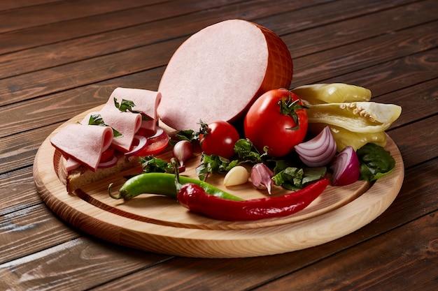 木製のテーブルの上の木製のプレートに野菜とハーブとモルタデッラ。