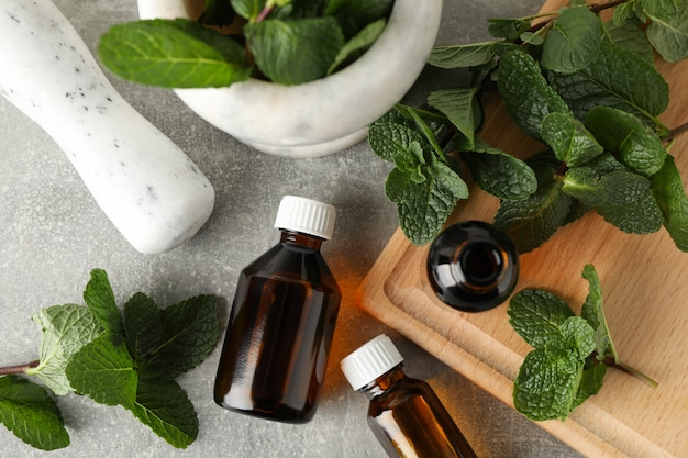 Mortar, medical bottles and mint on grey table, top view