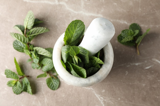 Mortar, pestle and mint on grey, top view