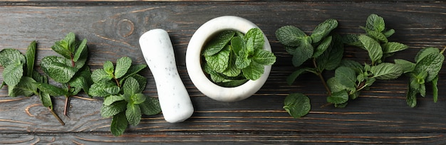 Mortar, pestle and mint on wooden, top view