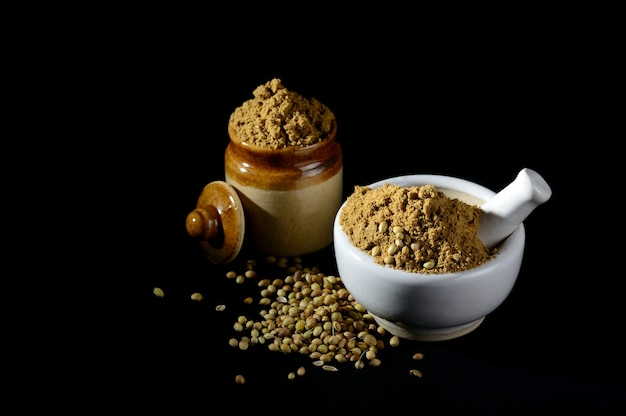 Mortar and pestle with coriander powder and seeds on black background.