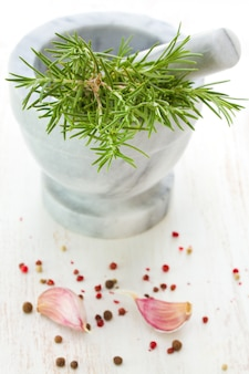 Mortar and pestle with rosemary and spices