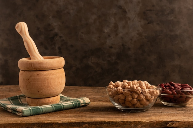 Mortar with pestle made of wood, 3 bowls of chickpea, red beans, lentil on the table