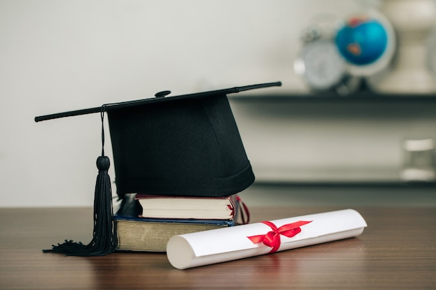 A mortarboard on books and graduation scroll on the desk.education learning concept