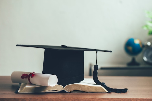 A mortarboard and graduation scroll on open books on the desk.education learning concept